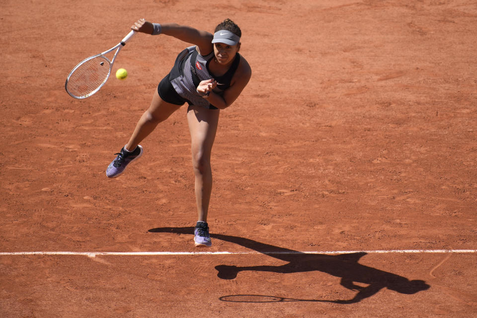 Japan's Naomi Osaka serves the ball to Romania's Patricia Maria Tig during their first round match of the French Open tennis tournament at the Roland Garros stadium Sunday, May 30, 2021 in Paris. (AP Photo/Christophe Ena)