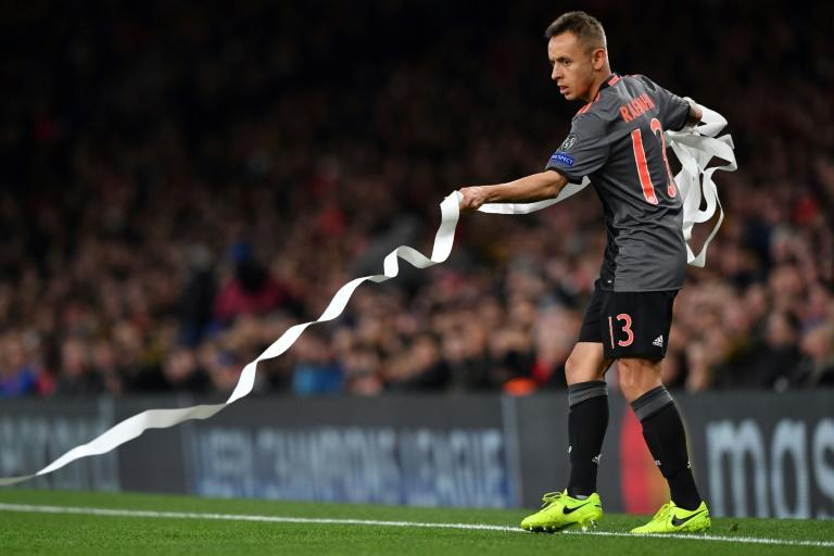 Bayern Munich's Brazilian defender Rafinha clears the pitch of toilet roll before the Champions League last 16 second-leg against Arsenal at The Emirates Stadium in London on March 7, 2017
