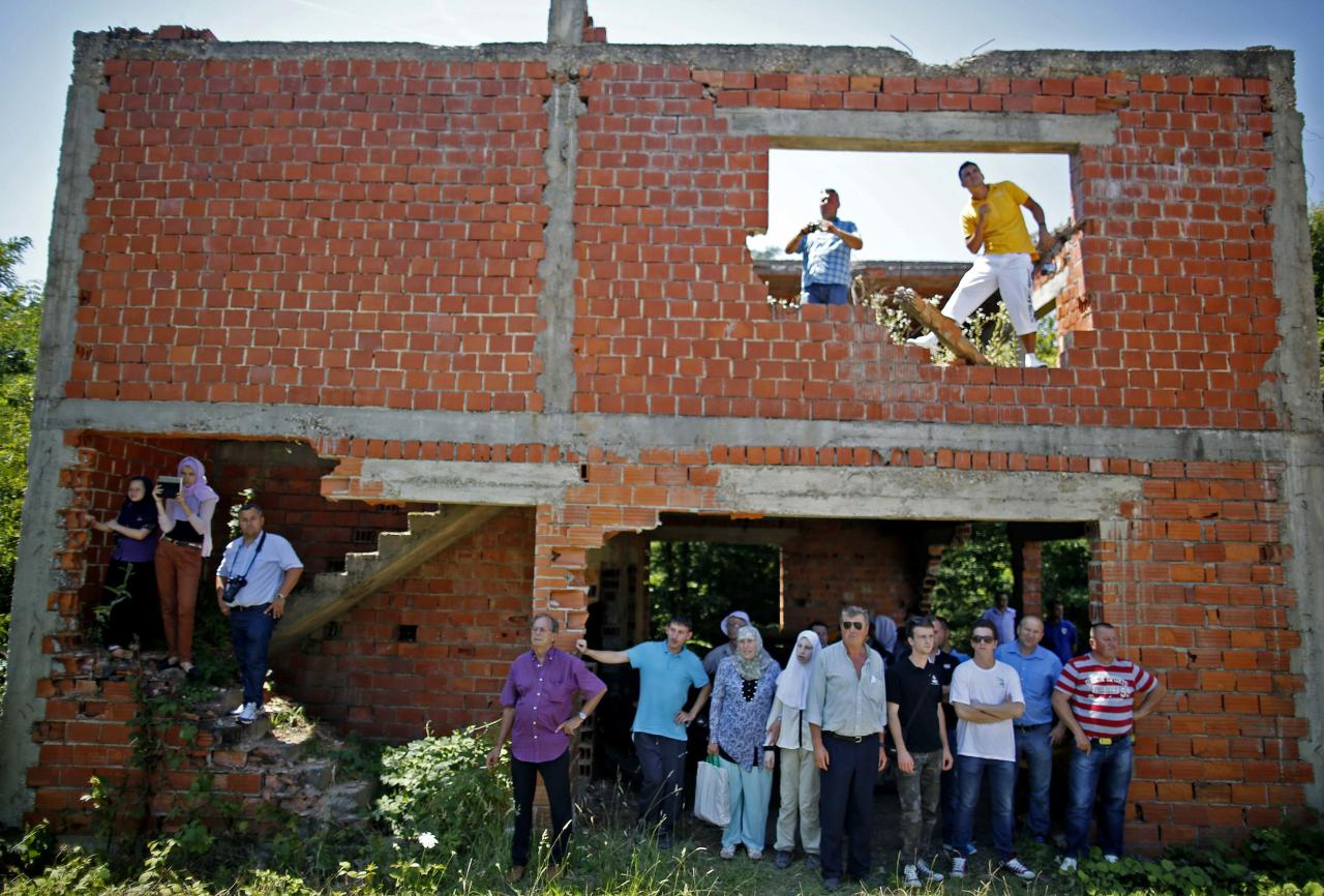 Bosnian Muslims watch a mass funeral from a war-torn house in the village of Biscani, near Prijedor July 20, 2014. Seventy seven Muslims were killed in Biscani village in the war. The collective burial of 284 Bosnian Muslims and Croats, whose remains were found and identified in a northwestern mass grave and believed to be the largest from Bosnia's 1992-95 war, will take place on Sunday. REUTERS/Dado Ruvic (BOSNIA AND HERZEGOVINA - Tags: POLITICS CIVIL UNREST CONFLICT RELIGION)