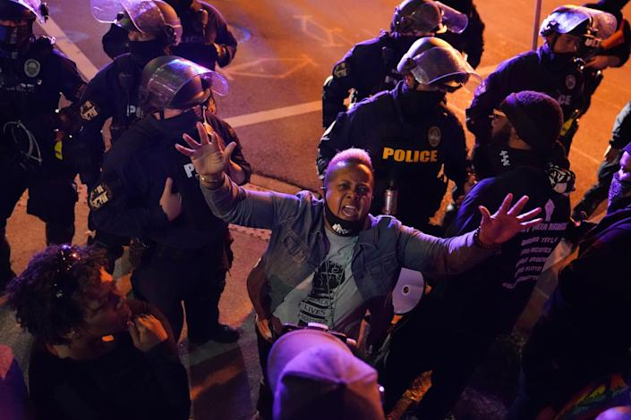 A woman shouts to police on Thursday night during protests following the decision not to charge three officers for murder of Breonna Taylor.