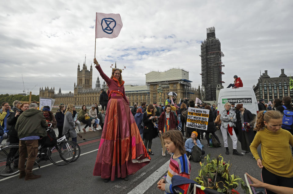 Climate protestors block Westminster Bridge leading to Britain's Parliament, rear, in central London Monday, Oct. 7, 2019, in an attempt to disrupt the heart of government. (AP Photo/Matt Dunham)