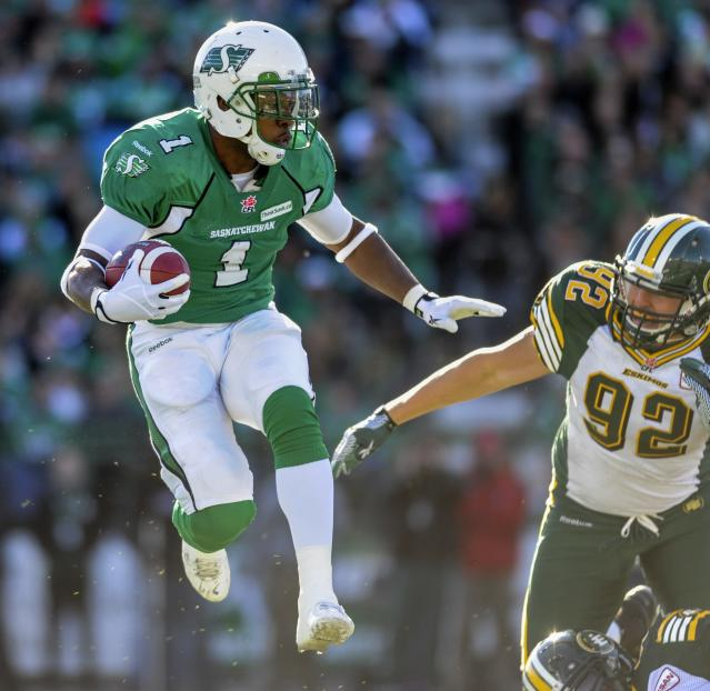 Saskatchewan Roughriders running back Kory Sheets (L) tries to get around Edmonton Eskimos defensive end Justin Capicciotti during the first half of their CFL football game in Regina, Saskatchewan October 12, 2013. REUTERS/Matt Smith (CANADA - Tags: SPORT FOOTBALL)