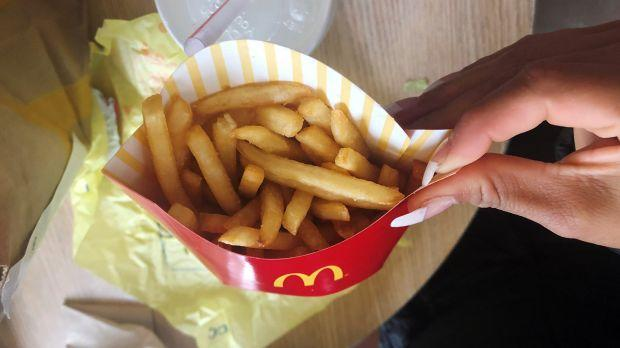 A McDonald's customer shows her french fries box at the fast-food chain McDonald's in New York