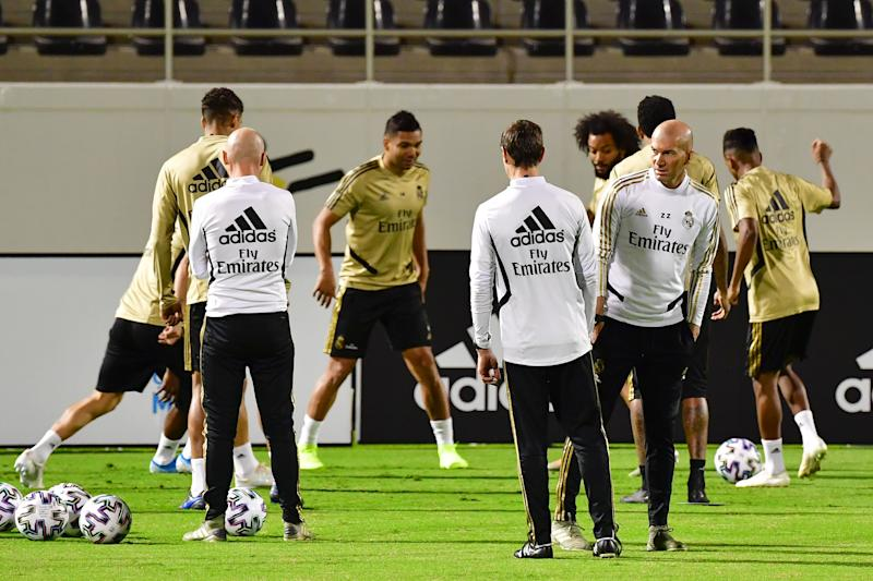Real Madrid's French coach Zinedine Zidane (R) speaks with Fitness coach Gregory Dupont (C) during a training session on the eve of the Spanish Super Cup semi final between Valencia and Real Madrid on January 7, 2020, at the King Abdullah Sport City in the Saudi Arabian port city of Jeddah. (Photo by Giuseppe CACACE / AFP) (Photo by GIUSEPPE CACACE/AFP via Getty Images)