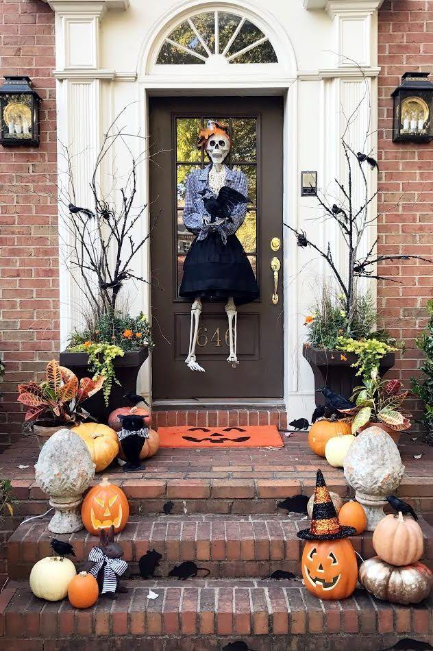"""<p>If the idea of greeting your trick-or-treaters with a skeleton feels a little too intense, follow this blogger's lead and dress it up in a cute outfit to tone down the """"scary"""" factor.</p><p><strong>Get the tutorial at <a href=""""https://www.thepinkclutchblog.com/2016/10/happy-halloween.html"""" rel=""""nofollow noopener"""" target=""""_blank"""" data-ylk=""""slk:The Pink Clutch"""" class=""""link rapid-noclick-resp"""">The Pink Clutch</a>.</strong></p><p><a class=""""link rapid-noclick-resp"""" href=""""https://go.redirectingat.com?id=74968X1596630&url=https%3A%2F%2Fwww.walmart.com%2Fsearch%2F%3Fquery%3Ddoor%2Bmats&sref=https%3A%2F%2Fwww.thepioneerwoman.com%2Fholidays-celebrations%2Fg32894423%2Foutdoor-halloween-decorations%2F"""" rel=""""nofollow noopener"""" target=""""_blank"""" data-ylk=""""slk:SHOP DOOR MATS"""">SHOP DOOR MATS</a></p>"""