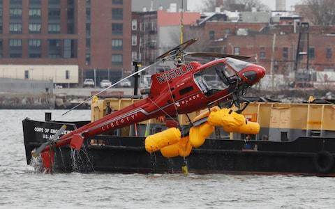 The wreckage of a chartered Liberty Helicopters helicopter that crashed into the East River is hoisted from the water in New York - Credit: Shannon Stapleton/Reuters