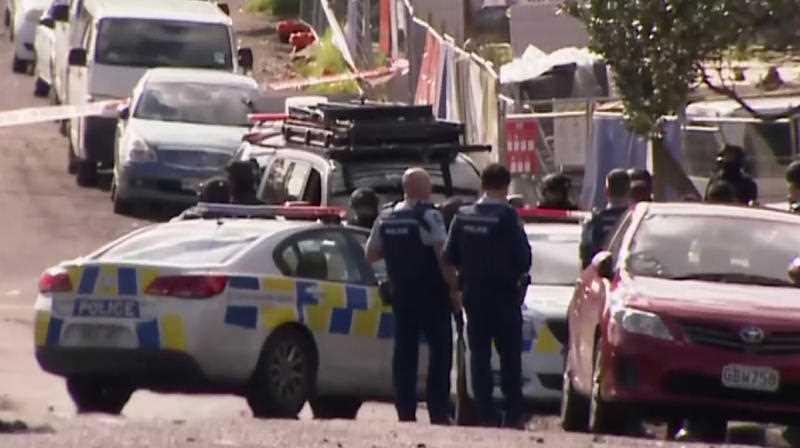 This image made from a video, shows armed police at the scene of a shooting incident following a routine traffic stop in Auckland, New Zealand.