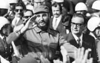<p>Cuban Prime Minister Fidel Castro waves to a cheering crowd as he leaves the airport at Santiago, Chile, with President Salvador Allende, Nov. 10, 1971. (AP Photo) </p>