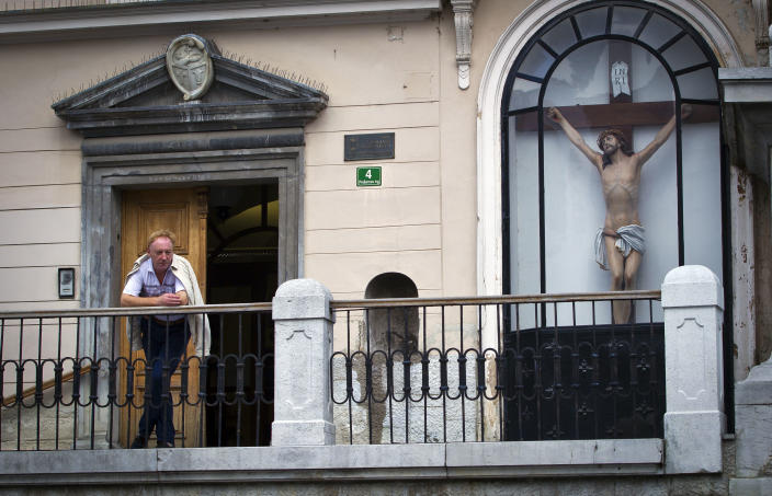 "A man looks from a terrace while standing next to a crucifix, in downtown Ljubljana, Slovenia, Tuesday, Sept. 25, 2012. Once the envy of the former European communist states because of its booming economy and Western-style living standards, Slovenia is becoming a showcase of failed transition, government mismanagement and bad loans. Andrej Plut has always thought he was fortunate to live in Slovenia, at one time the most prosperous of the former republics of Yugoslavia and a star among the eastern European states that joined the EU after the fall of communism. The 55-year-old dentist can't figure out what went wrong with his tiny Alpine state, which now faces one of the worst recessions and financial system collapses among the crisis-stricken 17-country group that uses the euro. ""We used to live so well,"" Plut said. ""Now, we don't know what tomorrow brings."" (AP Photo/Darko Bandic)"