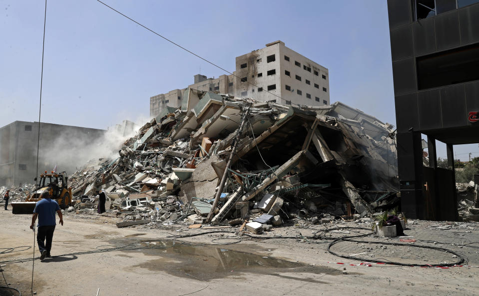 People inspect the rubble of a building that was destroyed by an Israeli airstrike on Saturday that housed The Associated Press, broadcaster Al-Jazeera and other media outlets, in Gaza City, Sunday, May 16, 2021. (AP Photo/Adel Hana)