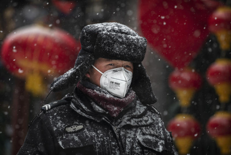 BEIJING, CHINA - FEBRUARY 05: A Chinese guard wears a protective mask as he walks during a snowfall in an empty and shuttered commercial street on February 5, 2020 in Beijing, China. China's stock markets tumbled in trading on Monday, the first day back after an extended Lunar New Year holiday as a mystery virus continues to spread in China and worldwide. The number of cases of a deadly new coronavirus rose to more than 20000 in mainland China Wednesday, days after the World Health Organization (WHO) declared the outbreak a global public health emergency. China continued to lock down the city of Wuhan in an effort to contain the spread of the pneumonia-like disease which medicals experts have confirmed can be passed from human to human. In an unprecedented move, Chinese authorities have put travel restrictions on the city which is the epicentre of the virus and neighbouring municipalities affecting tens of millions of people. The number of those who have died from the virus in China climbed to over 490 on Thursday, mostly in Hubei province, and cases have been reported in other countries including the United States, Canada, Australia, Japan, South Korea, India, the United Kingdom, Germany, France and several others. The World Health Organization has warned all governments to be on alert and screening has been stepped up at airports around the world. Some countries, including the United States, have put restrictions on Chinese travellers entering and advised their citizens against travel to China. (Photo by Kevin Frayer/Getty Images)