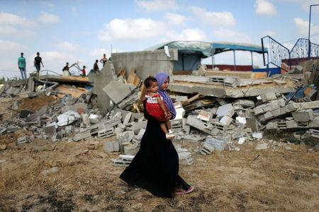 A Palestinian woman carries a girl as she walks past the site of an Israeli air strike, in Khan Younis in the southern Gaza Strip August 9, 2018. REUTERS/Ibraheem Abu Mustafa