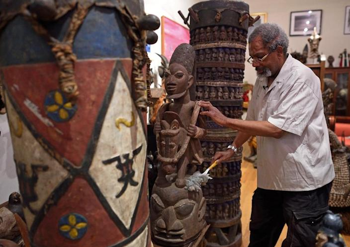 African art collector Eric Edwards dusts an Eppa helmet mask from Nigeria in his apartment in New York (AFP Photo/Don Emmert)