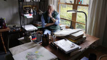 """Artist Robert Seaman pauses while sketching in his room at an assisted living facility Monday, May 10, 2021, in Westmoreland, N.H. Seaman, who moved into the facility weeks before the COVID-19 pandemic shutdown his outside world in 2020, recently completed his 365th daily sketch, or what he calls his """"Covid Doodles"""", since being isolated due to the virus outbreak. (AP Photo/Charles Krupa)"""