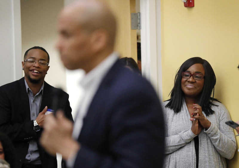 Former chairwoman of the Iowa Democratic Black Caucus Jamie Woods, right, listens as Democratic presidential candidate Sen. Cory Booker speaks during the Iowa Democratic Party Black Caucus Reception, Tuesday, April 16, 2019, in Des Moines, Iowa. In Iowa _ that's right _ black Democrats are more energized than they've been since Barack Obama's 2008 presidential campaign and are poised to make a mark on the 2020 race. (AP Photo/Charlie Neibergall)