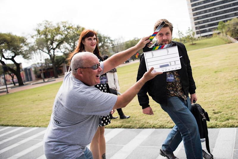 Brad Cowgill plays around by holding a film slate in front of Will Tooke and Emily McCombs.