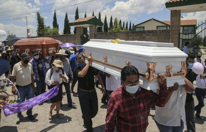 "<span class=""caption"">Funeral for a woman and her 11-year-old daughter, both found dead inside a burnt out vehicle in Puebla state, Mexico, June 11, 2020. </span> <span class=""attribution""><a class=""link rapid-noclick-resp"" href=""https://www.gettyimages.com/detail/news-photo/relatives-and-friends-of-gardenia-ortega-and-her-11-year-news-photo/1221065114?adppopup=true"" rel=""nofollow noopener"" target=""_blank"" data-ylk=""slk:Jose Castanares/AFP via Getty Images)"">Jose Castanares/AFP via Getty Images)</a></span>"