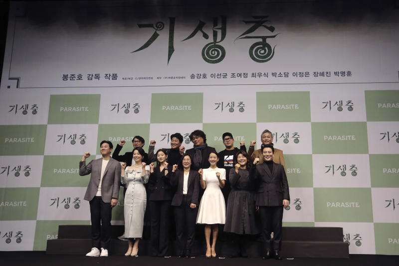 """Bong Joon-ho, director of Oscar-winning """"Parasite,"""" rear center, poses with the cast and crew after a press conference in Seoul, South Korea, Wednesday, Feb. 19, 2020. Bong said Wednesday """"the biggest pleasure and the most significant meaning"""" that the film has brought to him was its success in many countries though the audiences might feel uncomfortable with his explicit description of a bitter wealth disparity in modern society.  (AP Photo/Ahn Young-joon)"""