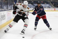 Chicago Blackhawks' Nikita Zadorov, left, and Columbus Blue Jackets' Max Domi chase the puck during the second period of an NHL hockey game Saturday, April 10, 2021, in Columbus, Ohio. (AP Photo/Jay LaPrete)