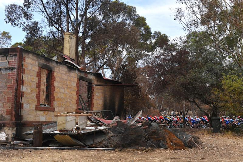 The 2020 Tour Down Under peloton passes the sad scene of a house destroyed by the bushfires during stage 2 between Woodside and Stirling