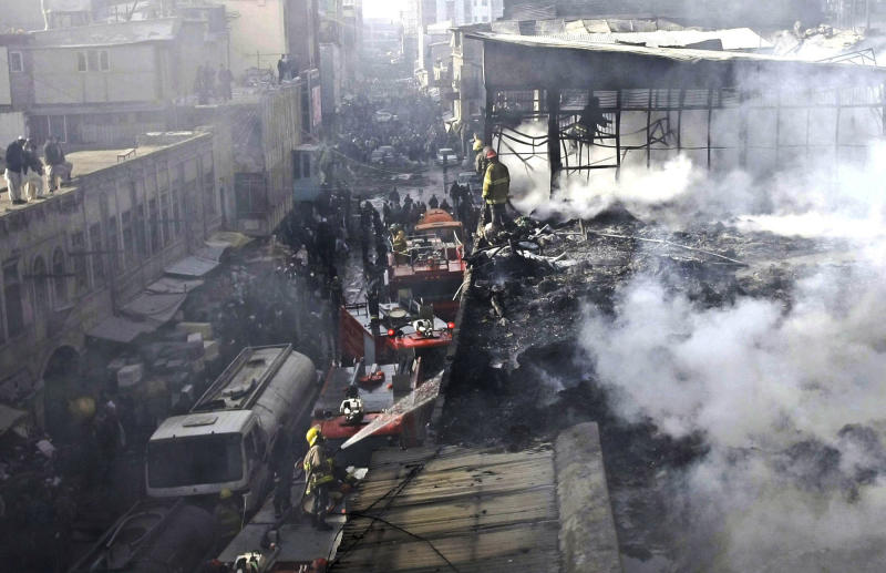 Afghan policemen and fire fighters investigate the scene of a burning market in Kabul, Afghanistan, Sunday, Dec. 23, 2012. Hundreds of shops at a market were burnt in a fire, but no causalities were reported. (AP Photo/Musadeq Sadeq)