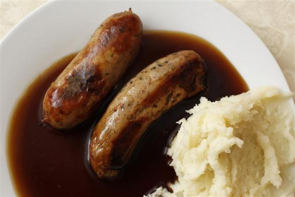 A traditional British meal of sausages and mashed potato in gravy, known as Bangers and Mash. Photographed at G. Kelly's pie and mash shop in east London.