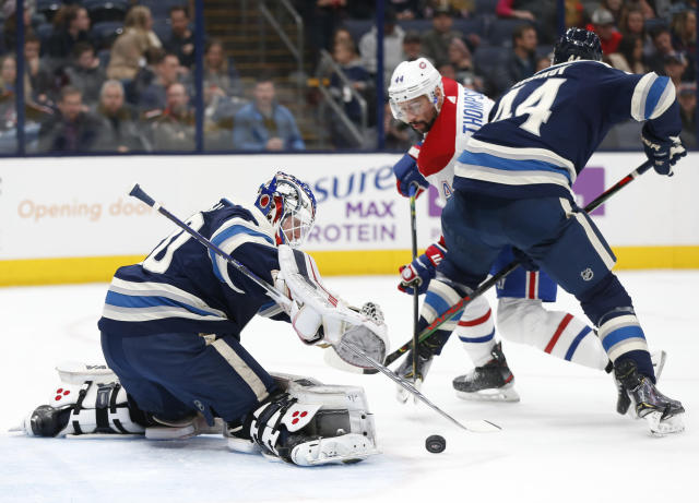 Columbus Blue Jackets' Joonas Korpisalo, left, of Finland, makes a save as teammate Vladislav Gavrikov, right, of Russia, and Montreal Canadiens' Nate Thompson fight for position during the first period of an NHL hockey game Tuesday, Nov. 19, 2019, in Columbus, Ohio. (AP Photo/Jay LaPrete)