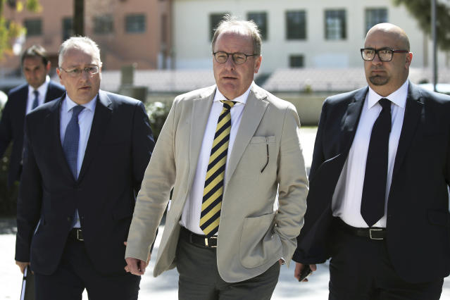 Austrian Herbert Huebel, center, chairman of the FIFA monitoring committee for the Hellenic Football Federation arrives for a press conference in Athens, Wednesday, March 14, 2018. FIFA has sent a delegation to Greece to discuss the country's soccer crisis, after the government indefinitely suspended top league matches. The suspension followed a pitch invasion by the gun-toting owner of PAOK Thessaloniki Sunday after a late goal for his team was disallowed by the referee. (AP Photo/Petros Giannakouris)