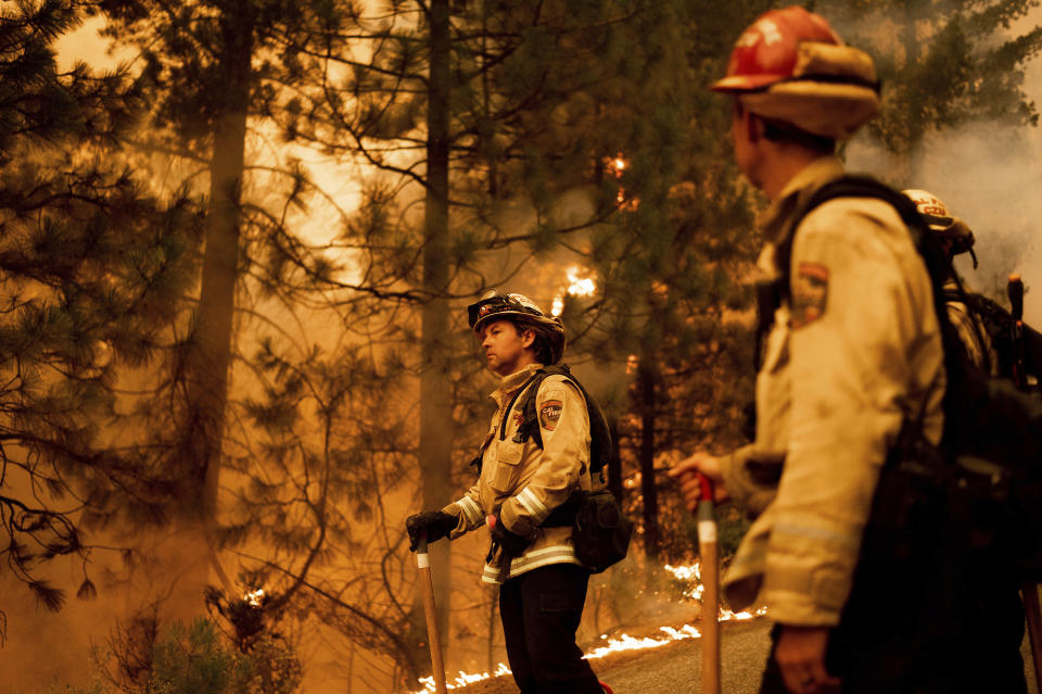 Firefighter Jason Prado monitors flames as his crew burns vegetation to stop the Dixie Fire from spreading near Prattville in Plumas County, Calif., on Friday, July 23, 2021. (AP Photo/Noah Berger)
