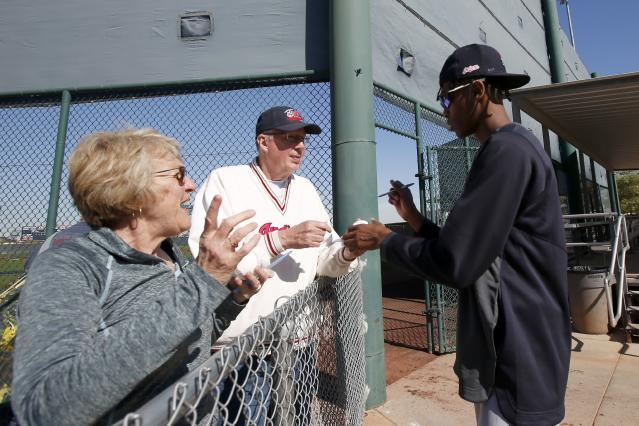 Cleveland Indians pitcher Triston McKenzie, right, gives autographs to fans during spring training baseball workouts for pitchers and catchers Friday, Feb. 14, 2020, in Avondale, Ariz. (AP Photo/Ross D. Franklin)