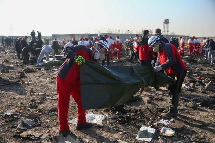 Red Crescent workers check plastic bags at the site where the Ukraine International Airlines plane crashed after take-off from Iran's Imam Khomeini airport, on the outskirts of Tehran