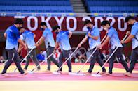 <p>Volunteers clean and disinfect mats during the judo competition during the Tokyo 2020 Olympic Games at the Nippon Budokan in Tokyo on July 24, 2021. (Photo by Franck FIFE / AFP)</p>