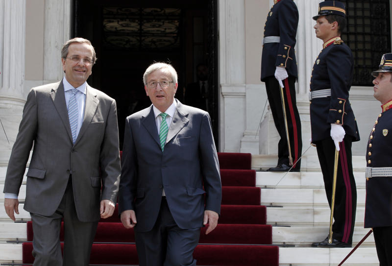Greek Prime Minister Antonis Samaras left, and Luxembourg Prime Minister and former Eurogroup chief Jean-Claude Juncker, exit the Maximou Mansion after their meeting in Athens, on Tuesday, June 11, 2013. Juncker arrived in Greece Monday for a three-day official visit.(AP Photo/Petros Giannakouris)