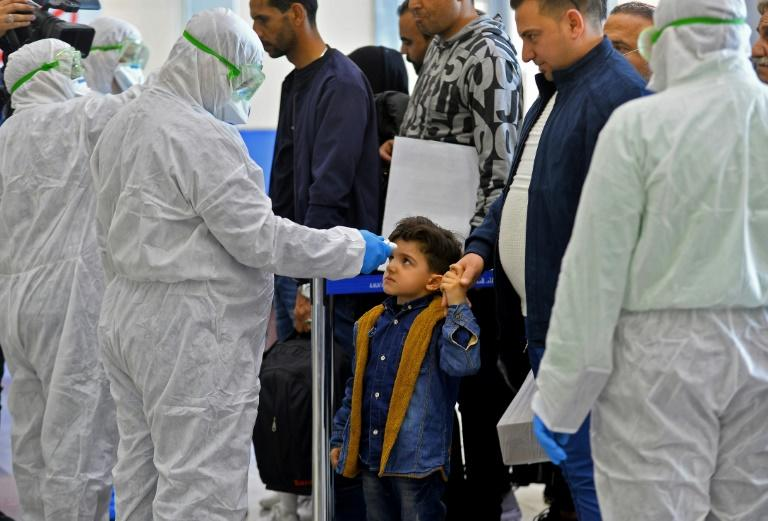 An Iraqi child's temperature is taken upon return from Iran at the Najaf International Airport on February 21