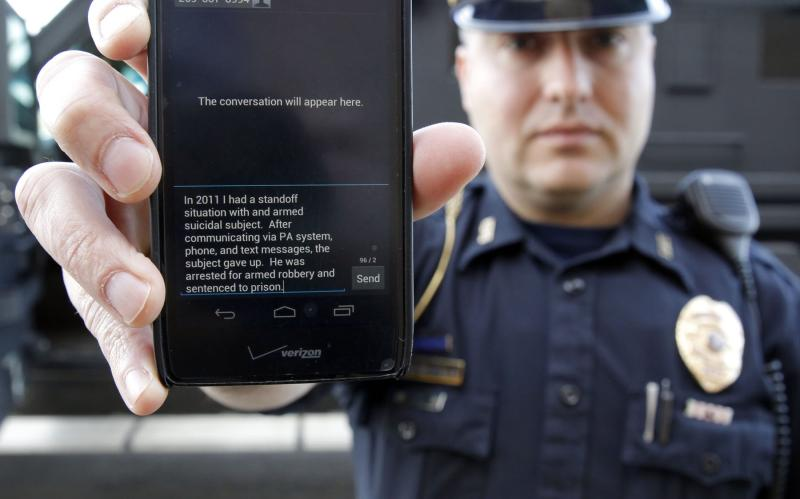 In a May 6, 2014 photo, Sgt. Andres Wells of the Kalamazoo Deptartment of Public Safety, who successfully used text messaging to negotiate with a suicidal robbery suspect during a 2011 standoff, shows his phone. With 6 billion text messages exchanged daily in the United States, texting is becoming a more frequent part of police crisis negotiations. (AP Photo/Mark Bugnaski)