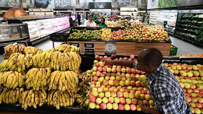 A shop assistant fills the shelves with fruits and vegetables at a store of Kenyan supermarket chain Naivas in Highridge, Nairobi, on January 18, 2018