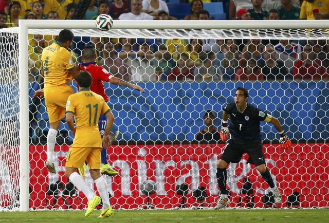 Australia's Tim Cahill (L) heads the ball to score a goal against Chile during their 2014 World Cup Group B soccer match at the Pantanal arena in Cuiaba June 13, 2014. REUTERS/Paul Hanna (BRAZIL - Tags: SOCCER SPORT WORLD CUP)