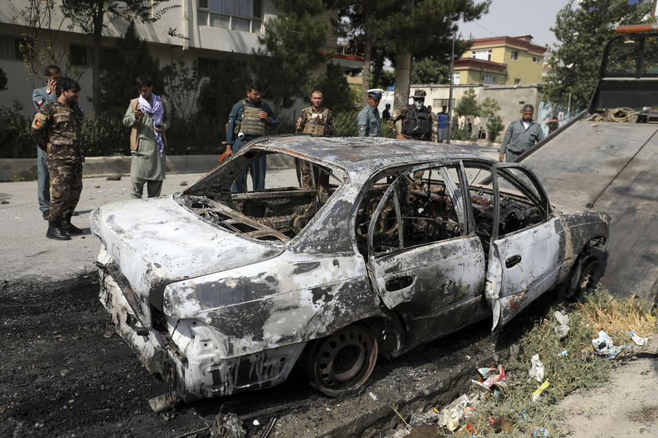 Security personnel inspect a damaged vehicle that was firing rockets in Kabul, Afghanistan, Tuesday, July 20, 2021. At least three rockets hit near the presidential palace on Tuesday shortly before Afghan President Ashraf Ghani was to give an address to mark the Muslim holiday of Eid-al-Adha. (AP Photo/Rahmat Gul)