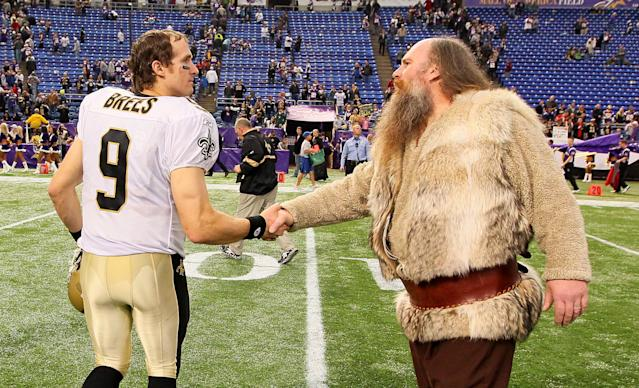 <p>(L-R) Drew Brees #9 of the New Orleans Saints shakes hands with Minnesota Vikings mascot Ragnar after the Saints defeated the Vikings 42-20 at the Hubert H. Humphrey Metrodome on December 18, 2011 in Minneapolis, Minnesota. (Photo by Adam Bettcher /Getty Images) </p>