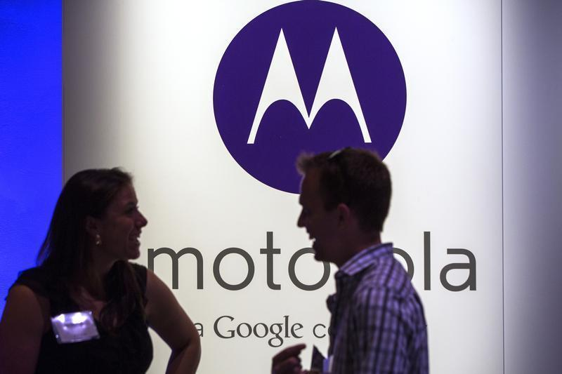A man and woman laugh in front of a Motorola logo at a launch event for Motorola's new Moto X phone in New York