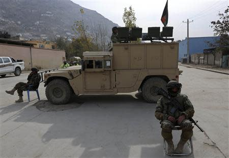 Afghan National Army (ANA) soldiers keep watch near a building in which the Loya Jirga (or grand council) is holding a committee session, in Kabul November 22, 2013. REUTERS/Omar Sobhani