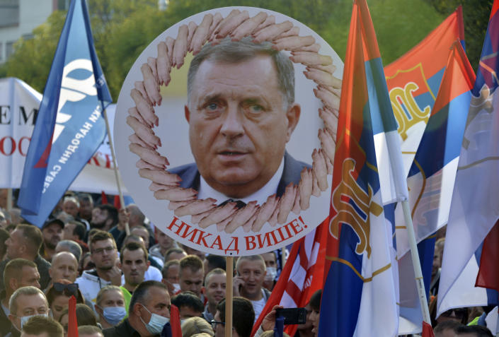 """A person holds a banner showing the Bosnian Serb member of the tripartite Presidency of Bosnia Milorad Dodik that reads: """"Never Again!"""", during a protest against the government in Banja Luka, in Serb-dominated part of Bosnia, Saturday, Oct. 2, 2021. Several thousand people have rallied against the government in Serb-dominated part of Bosnia. The protesters on Saturday accused the ruling party of nationalist leader Milorad Dodik of crime and corruption and called for its ouster. (AP Photo/Radivoje Pavicic)"""