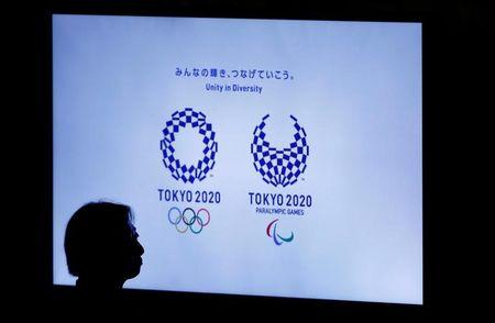 A woman is silhouetted against a monitor showing Tokyo 2020 Olympics and Paralympics emblems during the Olympic and Paralympic flag-raising ceremony at Tokyo Metropolitan Government Building in Tokyo