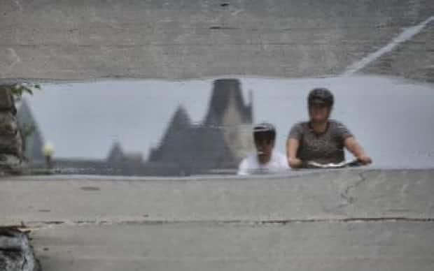 As viewed from a puddle, people can be seen cycling in downtown Ottawa on Tuesday. (Ian Black/CBC - image credit)