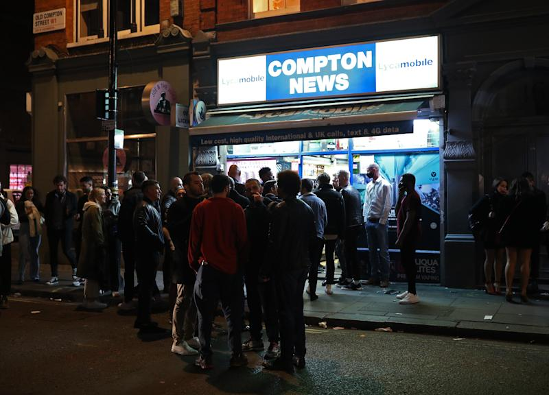 People queuing outside Compton News convenience store in Soho, London, after pubs and restaurants were subject to a 10pm curfew to combat the rise in coronavirus cases in England.