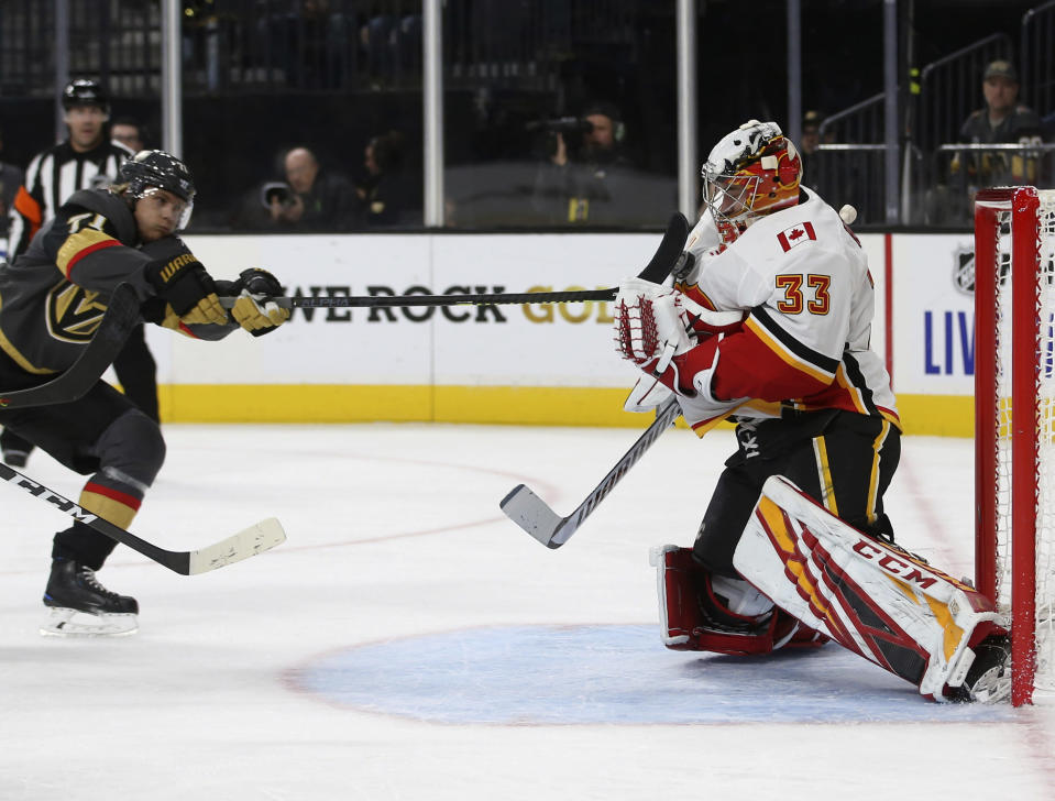 Vegas Golden Knights center William Karlsson (71) shoots on Calgary Flames goaltender David Rittich (33) during the second period of an NHL hockey game Saturday, Oct. 12, 2019, in Las Vegas. (AP Photo/Benjamin Hager)