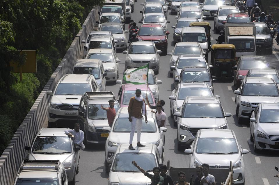 A man standing on the roof of a car as members of the Bharatiya Kisan Union (BKU) sit on protest against farm bills passed by the Parliament, blocking the Delhi-Noida border, on September 25, 2020 in Noida, India. The two bills - the Farmers (Empowerment and Protection) Agreement on Price Assurance and Farm Services Bill, 2020 and the Farming Produce Trade and Commerce (Promotion and Facilitation) Bill, 2020 - were passed by the Rajya Sabha despite uproar and strong protest by the Opposition parties in the house. (Photo by Sunil Ghosh/Hindustan Times via Getty Images)