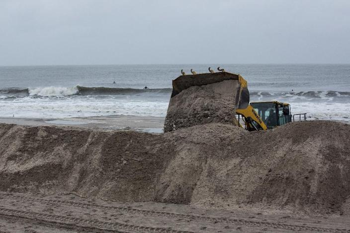 A bulldozer builds sand berms on the beach in preperation for Hurricane Joaquin on October 2, 2015 in Long Beach, New York (AFP Photo/Andrew Burton)