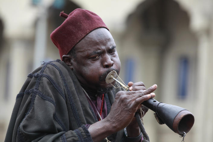 """A Nigeria muslim blows a horn during Eid al-Fitr celebration in Maiduguri, northeastern Nigeria, Thursday, Aug. 8, 2013. Nigerians in the birthplace of an Islamic uprising gripping the northeast celebrated the Muslim holy day of Eid al-Fitr on Thursday with devout prayers and a joyful show of adulation for their king that attracted more than 10,000 people. It was the first durbar in three years in the city of Maiduguri and the joy that it could take place - albeit amid massive security - was heard in the cries of ululating women, screams of delight from children and men chanting """"Long live the king!"""" (AP Photo/Sunday Alamba)"""