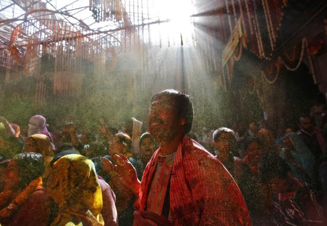 Hindu devotees react as priests (unseen) throw coloured powder on them during Holi celebrations at the Bankey Bihari temple in Vrindavan, in the northern Indian state of Uttar Pradesh, March 13, 2014. Holi, also known as the Festival of Colours, heralds the beginning of spring and is celebrated all over India. REUTERS/Anindito Mukherjee (INDIA - Tags: SOCIETY RELIGION)